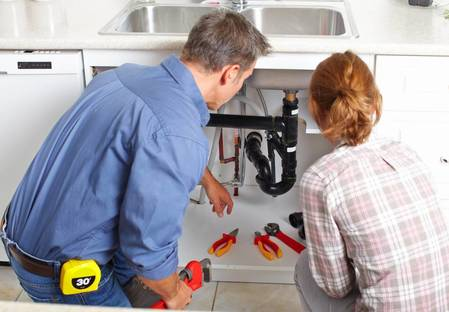 plumber and customer at kitchen sink